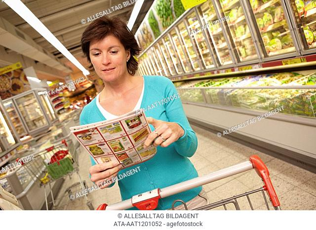 Woman studying special offers in the supermarket
