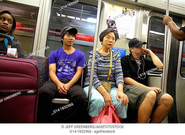 Massachusetts, Boston, South Boston, MBTA, T, Red Line, subway, inbound train, riders, Asian, man, woman, Black, sitting