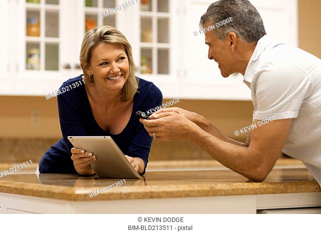 Caucasian couple using digital tablet and cell phone at kitchen counter