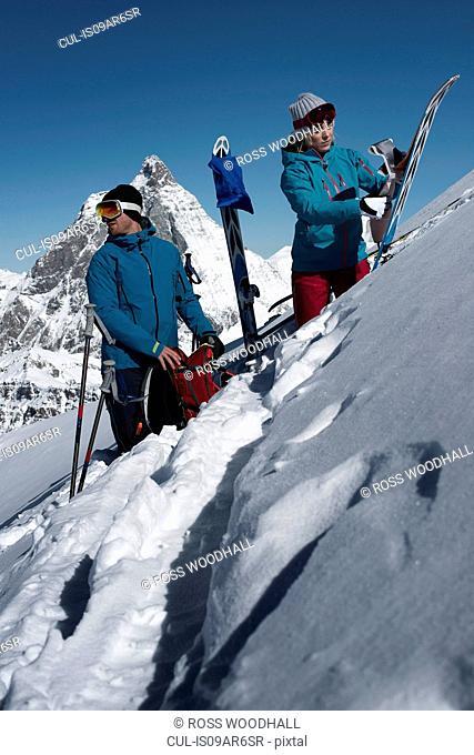 Couple with skis on mountain, Zermatt, Valais, Switzerland