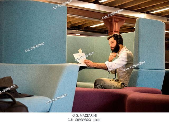Side view of man in booth wearing headphones looking at paperwork