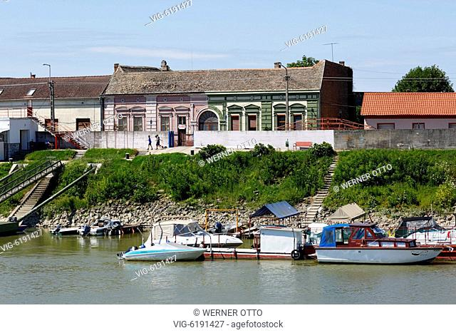 Hungary, Mohacs on the Danube, Transdanubia, Southern Transdanubia, Baranya county, Danube landscape, boats at the Danube bank, residential buildings - Mohacs