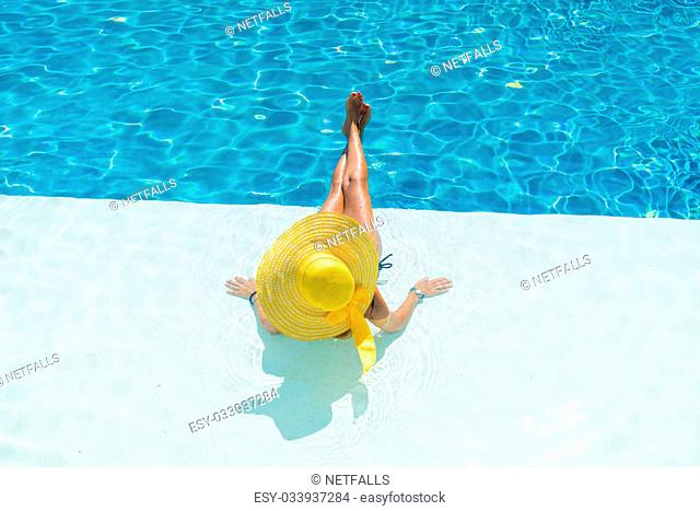 Young woman sitting on the edge of the swimming pool