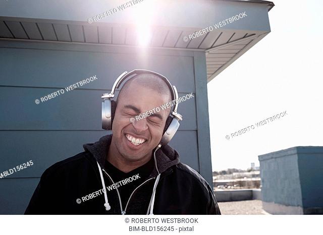 Mixed race man listening to headphones outdoors