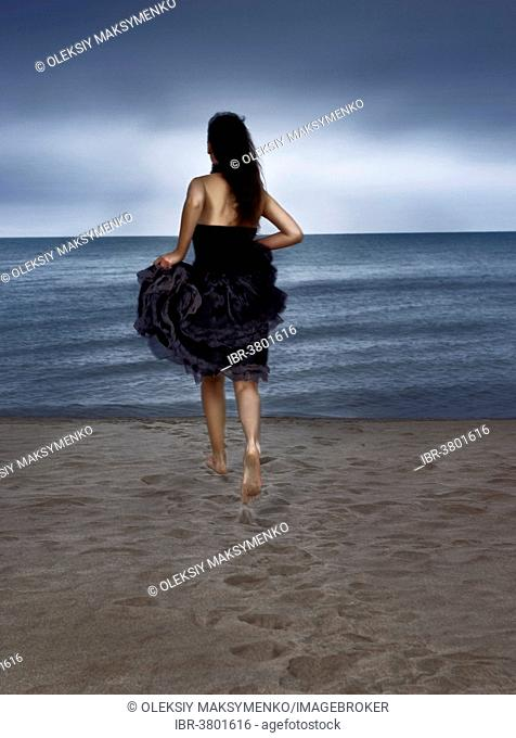 Young woman in black dress running towards the sea, rear view