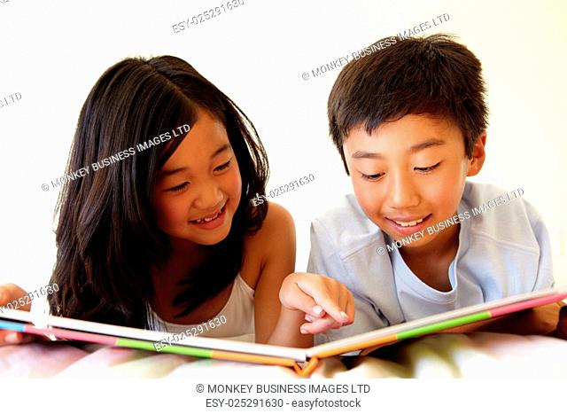 Young Asian girl and boy reading book