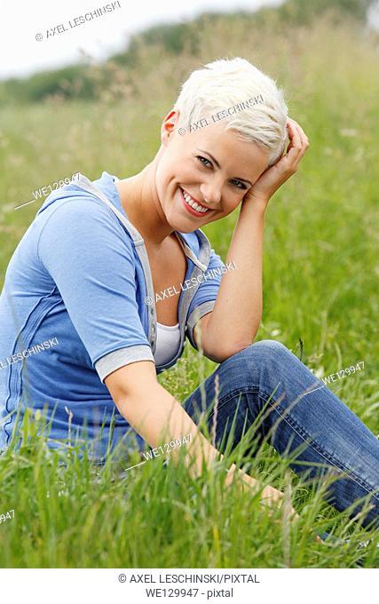 Young woman sitting in grass enjoying sun