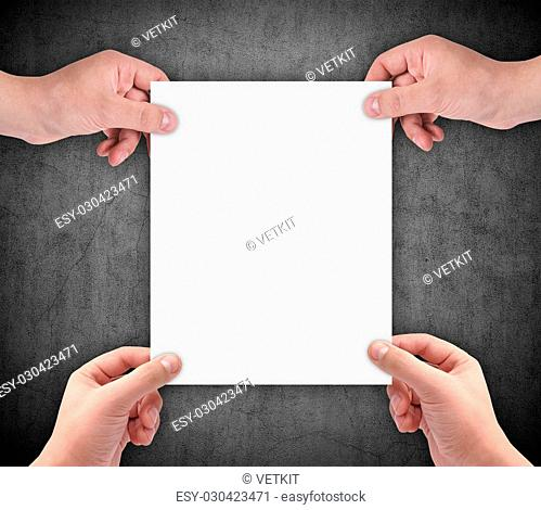hands holding blank paper on a gray wall background