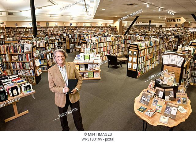 Portrait of a Caucasian male owner of a large bookstore, showing multiple racks of books in the background