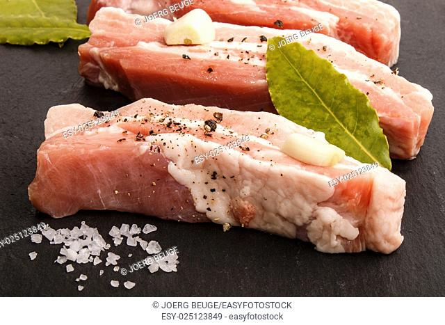 raw pork belly stripes with crushed black peppercorn, coarse salt, bay leaf and garlic on slate