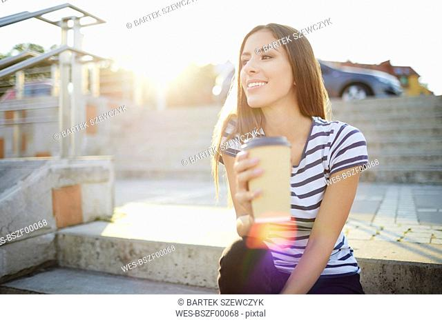 Young woman sitting on stairs outdoors and holding coffee