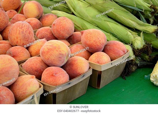 Ripe peaches and corn for sale at a local Farmers Market in rural Michigan, USA