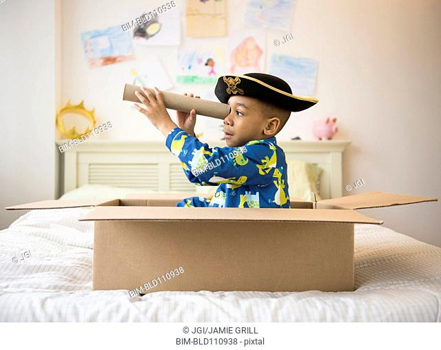 African American boy playing in cardboard box