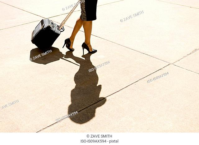 Businesswoman walking outdoors, wearing high heeled shoes, pulling wheeled suitcase, low section