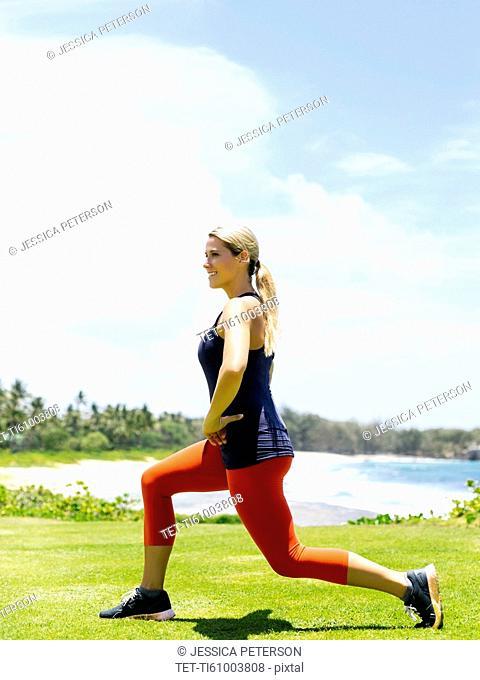 USA, Hawaii, Kauai, Woman exercising on beach