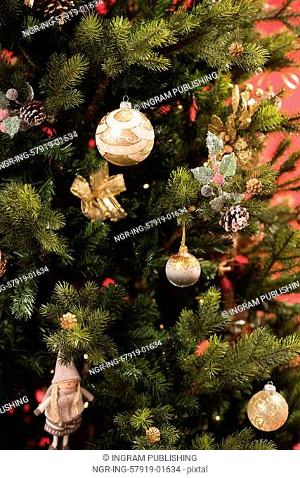 Christmas Tree on red background decorated with golden balls toys and bows
