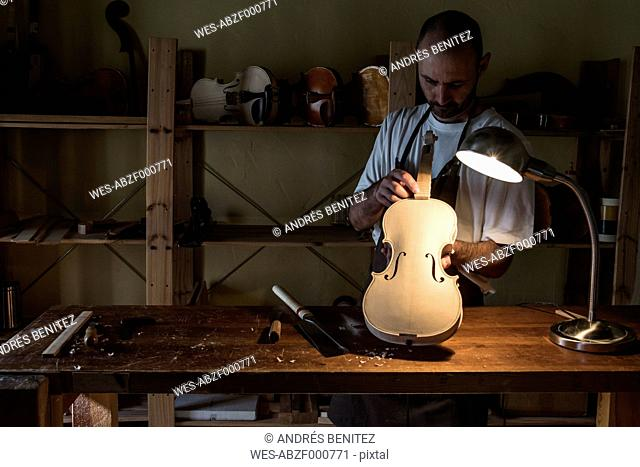 Luthier examining a violin in his workshop