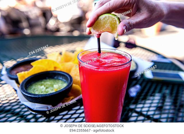 Frozen Strawberry daiquiri on a table at an outdoor restaurant with a woman's hand squeezing a lemon on top of the glass