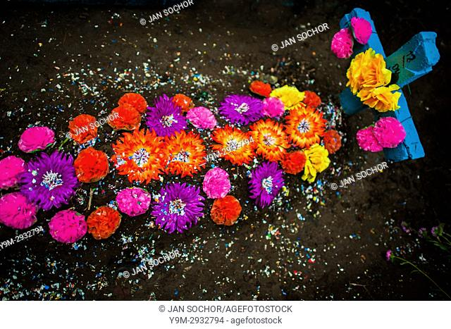 A gravesite, decorated with colorful paper flowers and confetti, is seen during the Day of the Dead festivities at the cemetery in Izalco, El Salvador