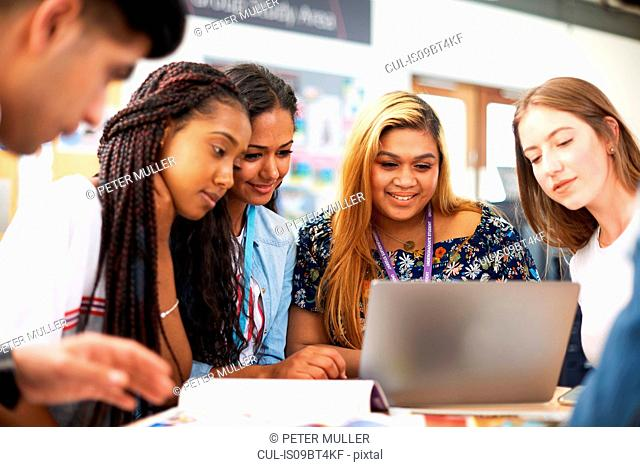 Female and male higher education students looking at laptop in college classroom