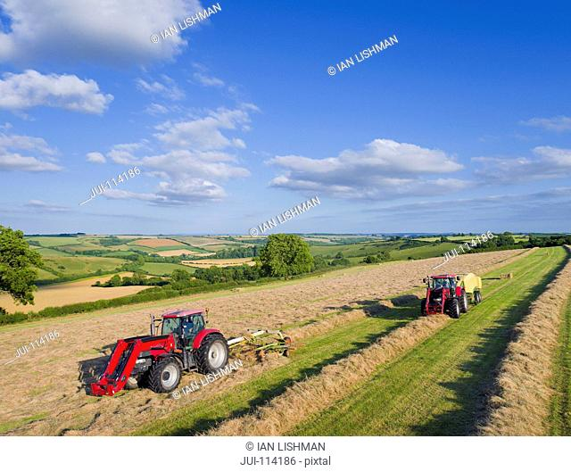 Aerial View Of Tractors Baling Hay In Field