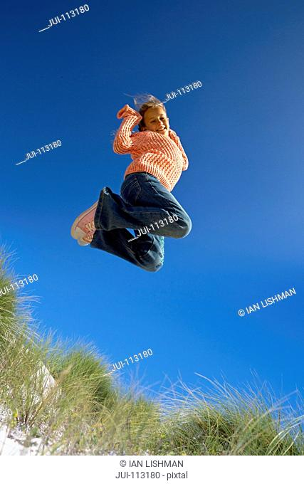 Exuberant girl jumping for joy over sand dune beach grass