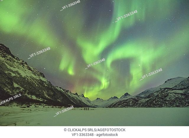 Northern lights with mountains and three people in winter. Kleppstad, Nordland county, Northern Norway, Norway