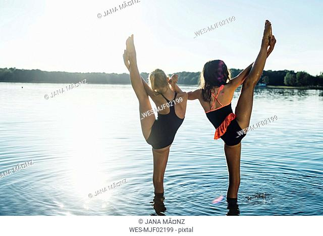Back view of two friends doing stretching exercise at lakeshore