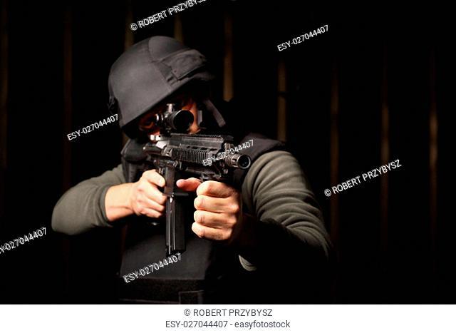 Militaria. Mezczyzna z karabinem ubrany w kamizelke kuloodporna i helm