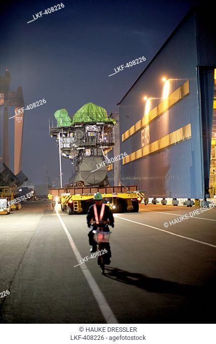 Moped driver leading a giant flatbed truck that is transporting MAN two-stroke engine from the test bed to the dry-dock, modular production at the laargest...
