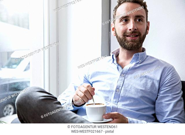 Young man with cup of coffee at the window