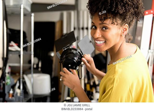 Black photographer adjusting lamp in studio