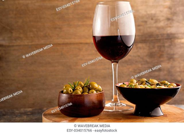 Olives served in bowls by wineglass on table