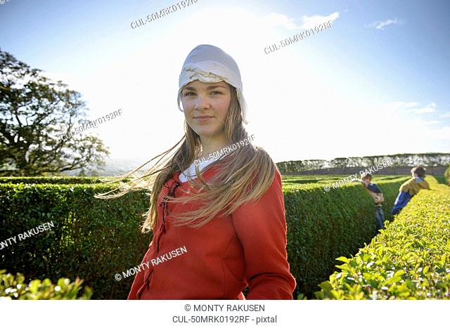 Student in period dress in hedge maze