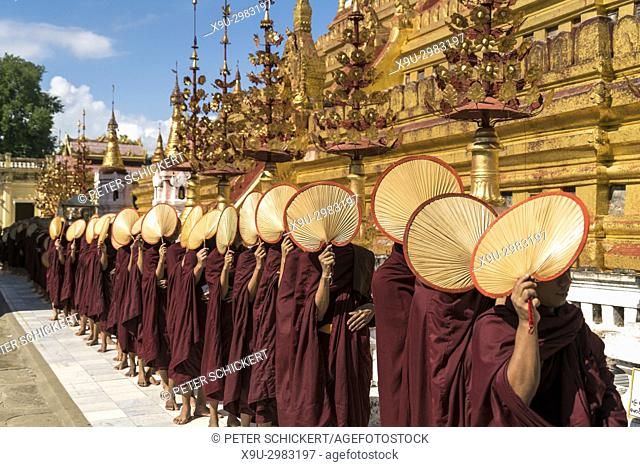 row of monks with their fan lining up for alms and donations, Shwezigon Pagoda, Bagan, Myanmar, Asia