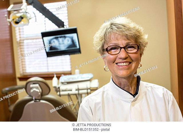 Caucasian dentist smiling in office