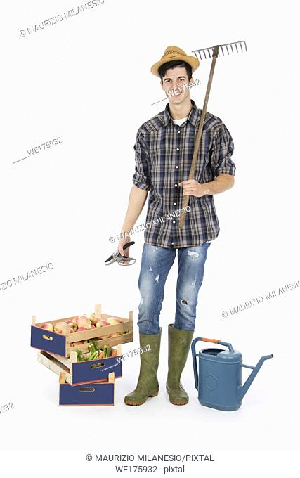 Young farmer with shears in hand and rake on his shoulder, at his feet crates with fruit and vegetables, he is wearing a straw hat