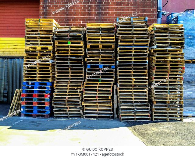 Brooklyn, New York City, USA. Stack of colorful pallets, stacked against an industrial building's wall