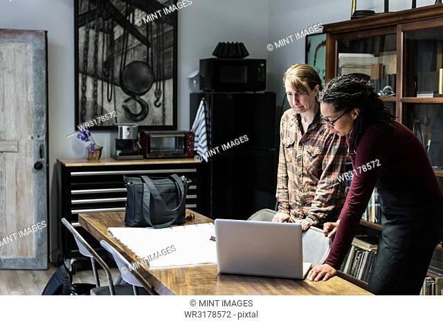 Two women gathered around table in office area of a metal workshop, looking at laptop