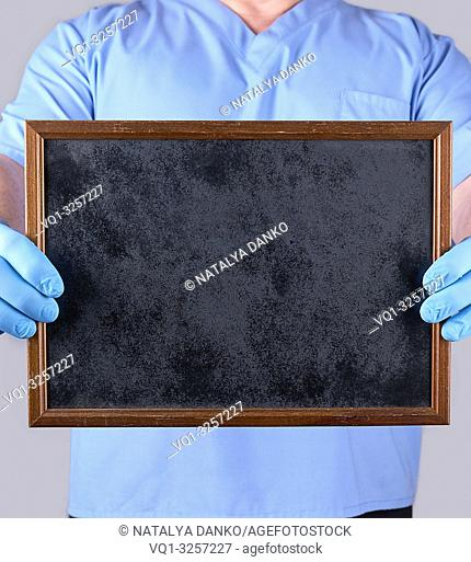 doctor in blue uniform and latex sterile gloves holding a blank black frame, selective focus