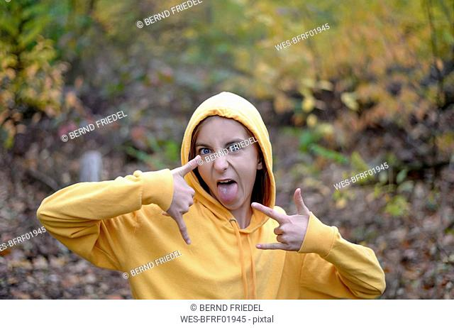 Portrait of girl wearing yellow hooded jacket in forest showing Rock And Roll Sign and sticking out tongue