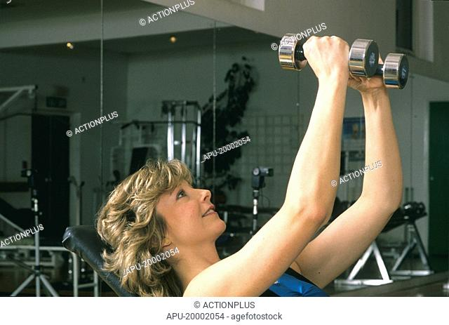Woman working with hand weights in a gym