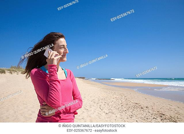 portrait of brunette woman looking side with pink sweater smiling and talking on mobile phone smartphone at beach with sea and blue sky behind