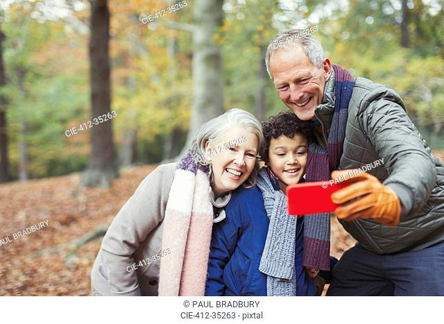 Grandparents and grandson taking selfie in autumn woods