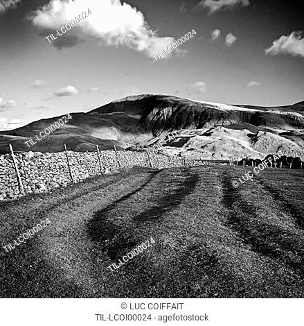 A field surrounded by a traditional stone wall with hills and clouds