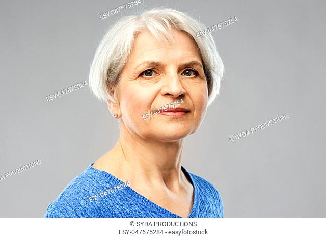 portrait of senior woman in blue sweater over grey