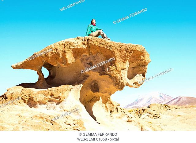 Woman sitting on the top of a rock