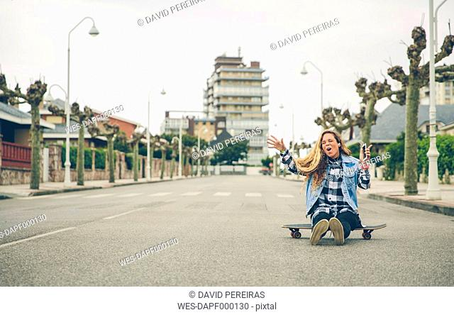 Carefree young woman listening to music sitting on skateboard