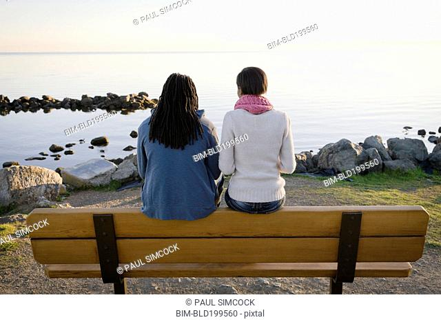 Black couple sitting on bench near shore