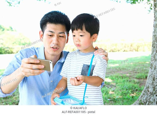 Happy Japanese father and son catching insects in a city park